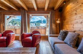Living room with a view over the Alps and two red sofas in Abachi luxury chalet in Les Gets