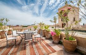 Rooftop terrace with table and chairs at luxury Adilah riad in Marrakech