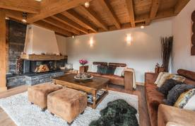 Living room with brown leather couches and chimney at Omaroo I luxury chalet in Morzine