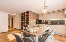 White open kitchen with wooden dining table and library at Sugi accommodation in Morzine