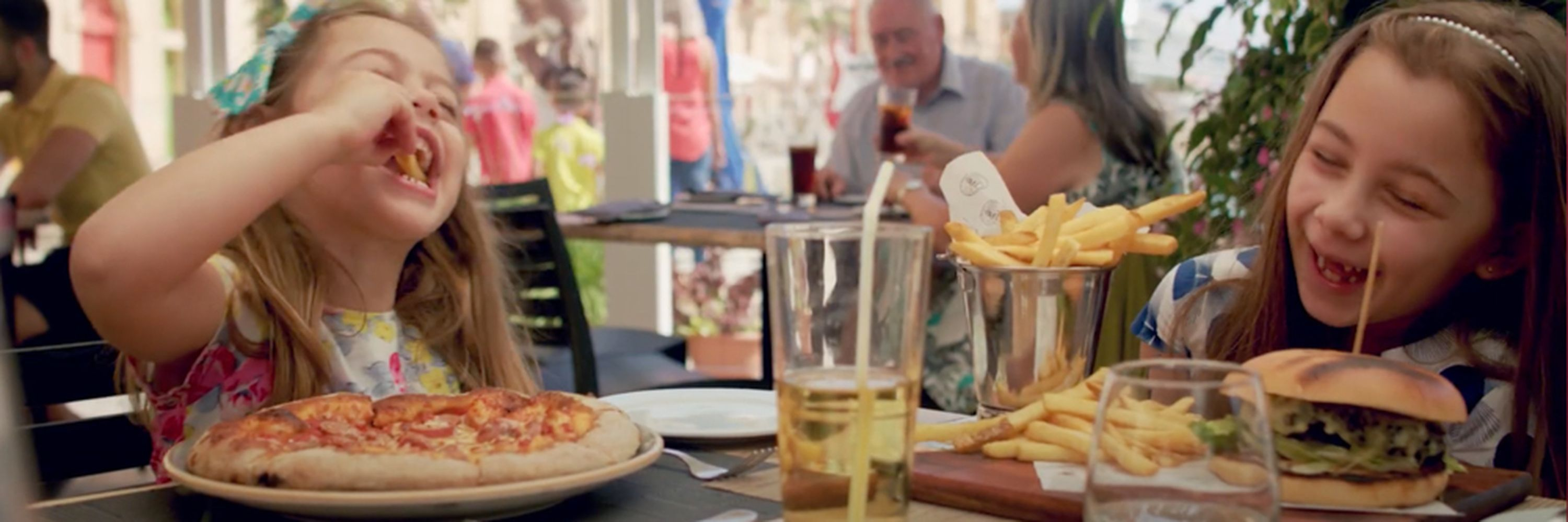 Two girls are eating at a table, one stole a fry from the other in motion blur's commercial