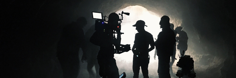 film crew in a dark tunnel