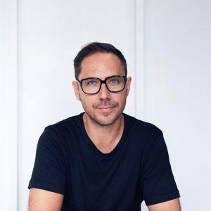 portrait photo of Jonny Niesche sitting in his studio
