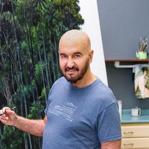 Tomas Sanchez smiling and holding a paintbrush