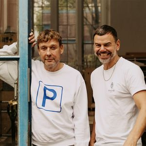 Two artists Elmgreen & Dragset smiling in a doorway