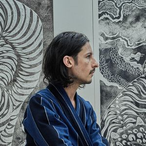 Side-profile of Kour Pour with his art behind him