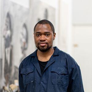 headshot of artist in his studio wearing dark blue overalls