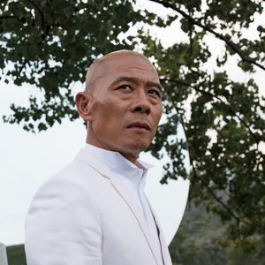 artist wearing white jacket and shirt gazing into distance above the camera