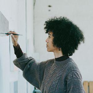 a portrait image of an artist Thenjiwe Niki Nkosi painting in her studio
