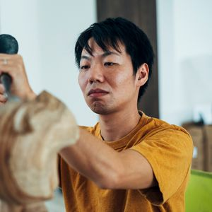 Satoru Koizumi concentrating on a sculpture in front of him