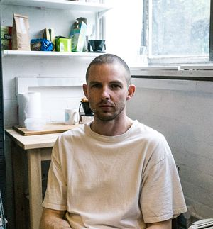 Elliot Dodd in a white t-shirt looking at the camera