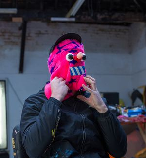 artist wearing black jacket with his hands clutching a pink mask which covers his face