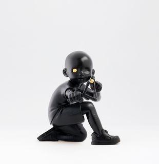 Black sculpture of kneeling boy with a slingshot and a golden eyeball