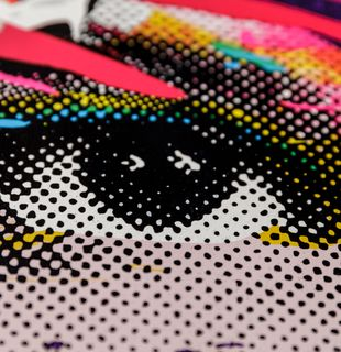 close-up of a print of an eye with coloured splashes of paint