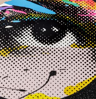 close-up of a print of an eye with a black glitter border and coloured details