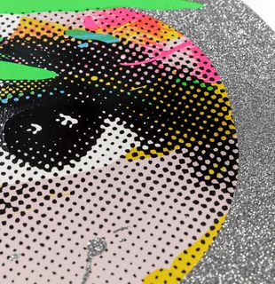 close-up of a print with a large eye central and a silver glitter border