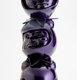 a purple sculpture of three heads in custom helmets stacked on top of each other by Hebru Brantley - close up middle
