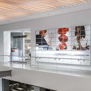 View of the outside of one of the studios within the Coty facility. Images of two women and nailpolish are printed on lit panels with white System 1224 panels lined along them showcasing various beauty products.