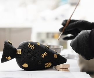 gloved hands holding a paintbrush, applying gold detail to a black sculpture