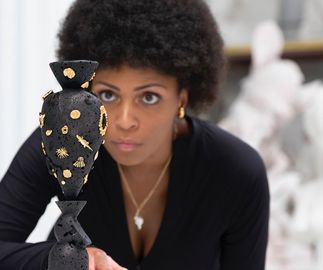 artist wearing gold jewellery inspecting a basalt sculpture from behind a table