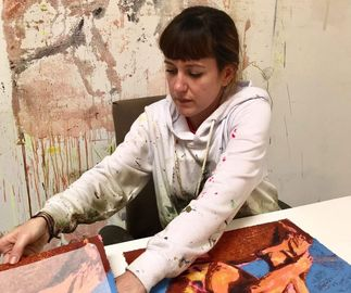 Claire Tabouret moving a print on a table in front of her