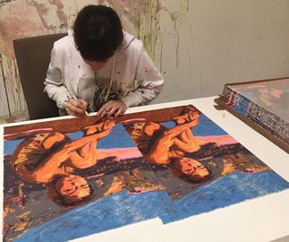 Claire Tabouret signing the bottom of two prints on a table