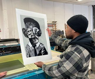 artist Neo Matloga holding his print, at the printing place