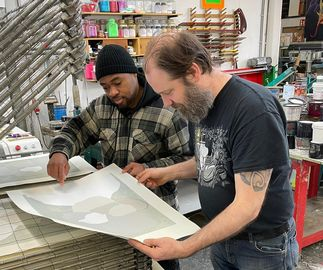 artist Neo Matloga proof checking his print, at the printing place - close up