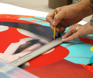 in production shot of a circular print of a woman's face with red glitter by Paul Insect