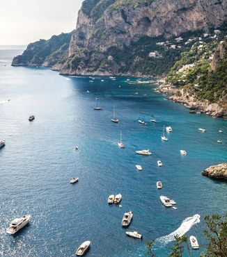 boats riding by coastline of island of capri in italy