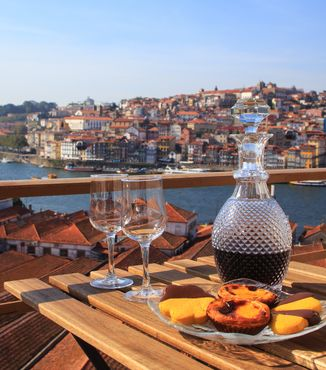 two glasses and vase of port wine on table roof top in porto portugal