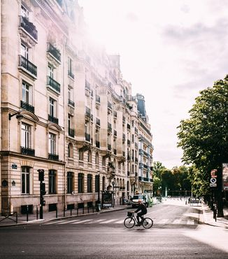 cream building with green trees lined up on a street in paris