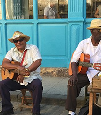 four cuban musicians sitting outside a bright blue building in havana