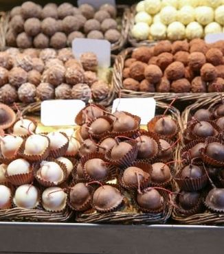 variety of chocolate covered cherries in baskets at a market