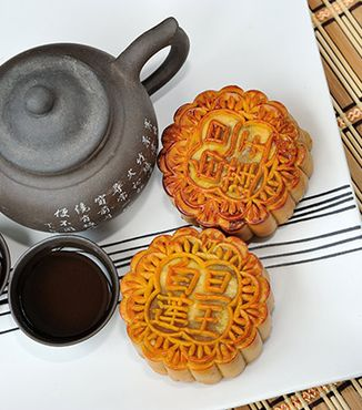 chinese kettle with two cups and two mooncakes on a white dish
