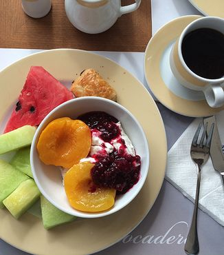 over head view of plate of fruit with yogurt and pastry with a cup of coffee