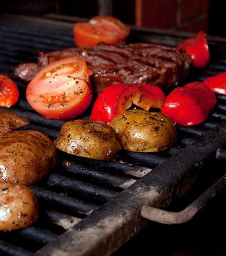 steak tomatoes and potatoes on a grill
