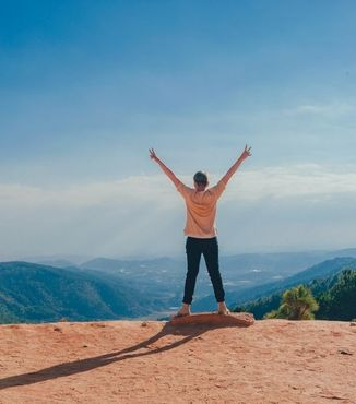 woman standing on a cliff facing valley with arms raised in the air