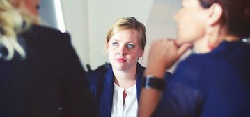 A woman in a suit looking at two interviewers