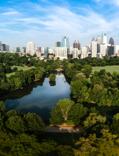 City skyline of Atlanta with Piedmont Park and the lake in the morning sun.