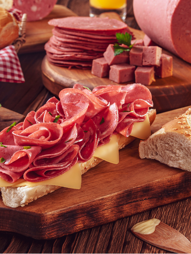 Mortadella sandwich with butter, bread and spices on wood cutting board