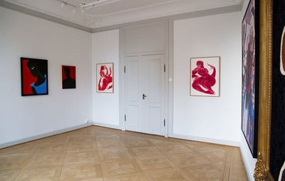 installation view of white walls with four paintings hung on them, two of which feature red figures on white backgrounds and flank a doorway