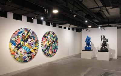 Installation view of two sculptures and two circular paintings
