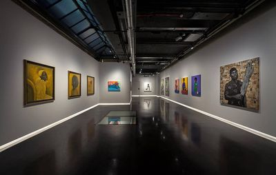 installation view of large exhibition space with various paintings hung on each wall