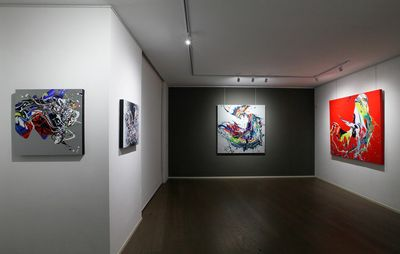 installation view of white and black walls with four paintings hung on them