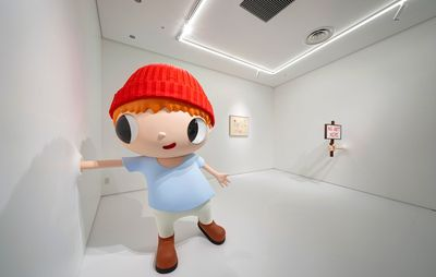 installation view of white exhibition space with a large cartoon sculpture of a boy sticking his hand into one of the walls