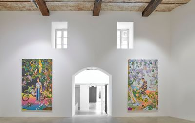 central door flanked by two large colourful paintings against white walls