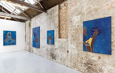 installation view of a brick wall with three blue paintings on it