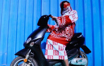 woman on black moped wearing white and red dress with heart shaped sunglasses on