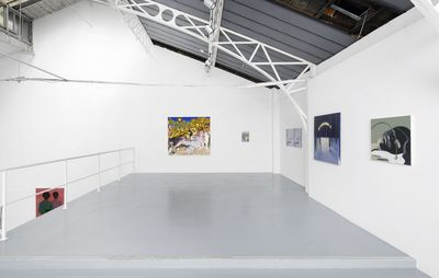 installation view of spacious room with white walls where five paintings of various sizes are hung up